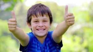 stock-footage-smiling-child-placing-his-thumbs-up-in-a-park